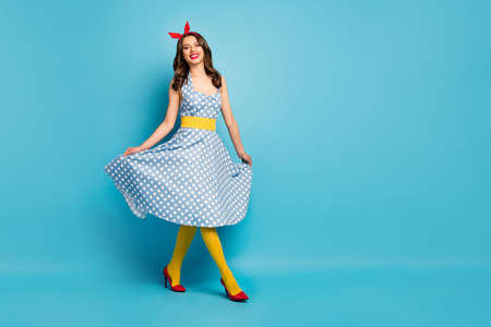 Full size photo of cheerful content charming lovely girl enjoy spring free time holiday touch polka-dot skirt wear pop shine pantyhose tights high-heels isolated blue color background