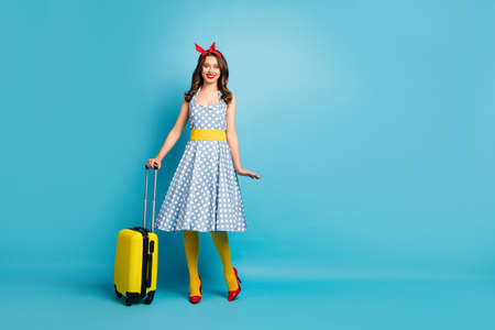 Full length body size view of her she nice attractive lovely pretty cheerful cheery wavy-haired girl carrying suitcase adventure isolated on bright vivid shine vibrant blue color background