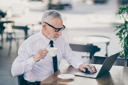 Profile photo of optimistic grey hair old business man drink tea write laptop wear spectacles white shirt outdoors near work center