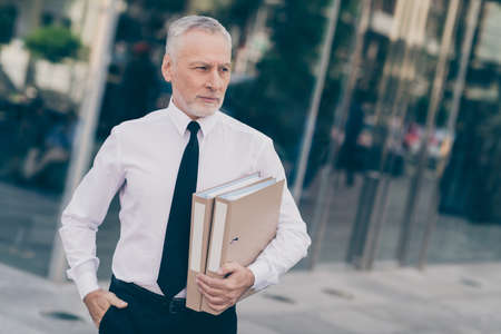 Photo of attractive confident mature worker man wear formal shirt walking holding paper folders outdoors city street