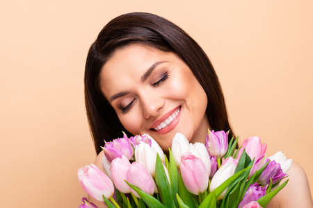 Photo of peaceful beautiful young woman hold flowers shoulders salon treatment isolated on beige color background