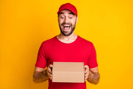 Photo portrait of funny laughing man delivering carton package in red clothes isolated on vivid yellow color background