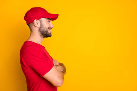 Profile side view portrait of nice cheerful content guy skilled mailman folded arms copy space isolated over bright yellow color background