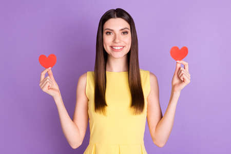 Portrait of attractive cheerful girl holding in hands two heart shape form isolated over violet purple pastel color background