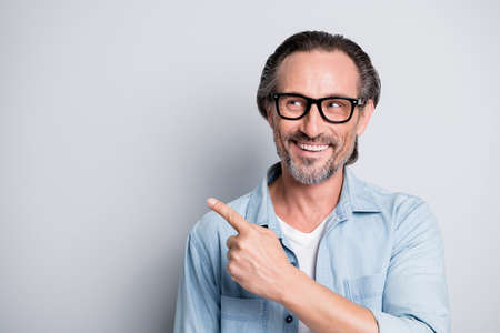 Photo of handsome man happy smile look point finger empty space advert promo select recommend isolated over grey color background