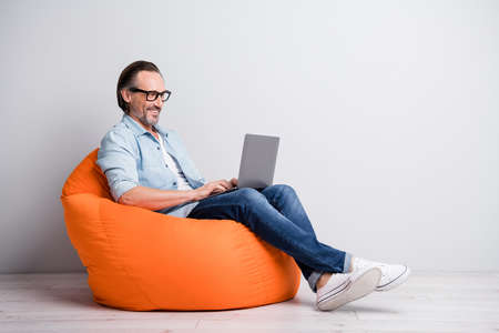 Profile side view of handsome clever cheerful mature man sitting on bean chair using laptop isolated over grey pastel color background