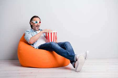 Full length photo of handsome man sit chair wear 3d glasses eat popcorn watch film isolated over grey color background Foto de archivo