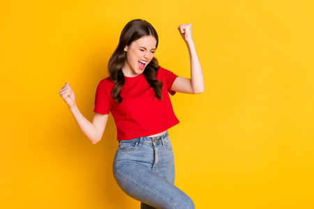 Lady raise fists hands win lucky day wear casual red t-shirt crop top isolated yellow color background