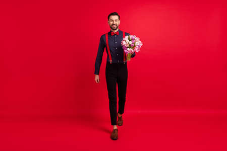 Full size photo of young handsome cheerful positive boyfriend hold bouquet go to date isolated on red color background