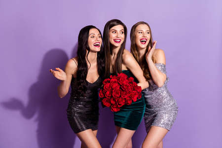 Photo of three flirty ladies hold bunch roses look side empty space wear mini dresses isolated purple color background