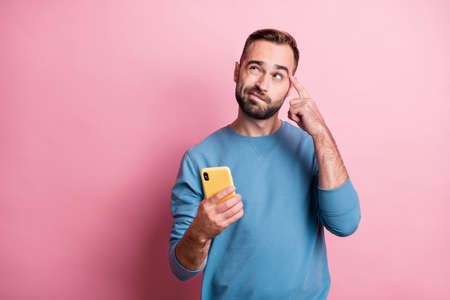 Photo of doubtful young man dressed blue sweater holding modern device looking empty space isolated pink color background