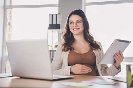 Photo portrait of pregnant woman holding tablet watching videos on laptop in modern office