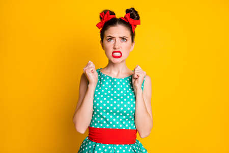 Photo of frustrated girl look up copyspace raise fists angry isolated over vibrant color background