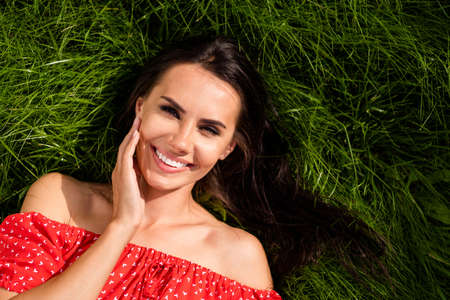 Photo of charming sweet young lady wear red off-shoulders dress resting green grass arm cheek outside countryside