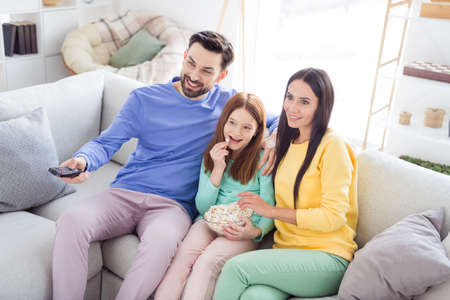 Photo of young family mom dad daughter happy positive smile eat popcorn watch movie sit sofa home remote controller