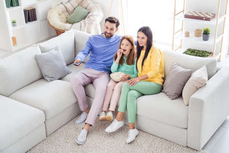 Top above high angle view full body photo of family happy positive smile sit couch indoors watch film eat popcorn remote controller Foto de archivo