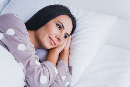 Photo of sweet shiny young lady sleepwear lying pillow arms cheekbone smiling indoors room home Stock Photo