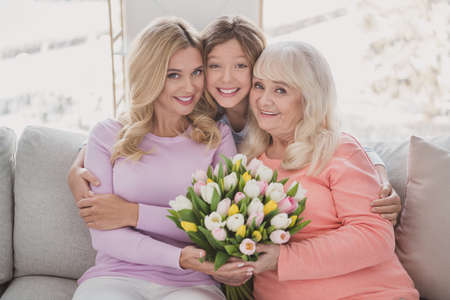 Photo portrait of grandmother daughter granddaughter spending time together hugging sitting on couch with tulips bunch Stock Photo