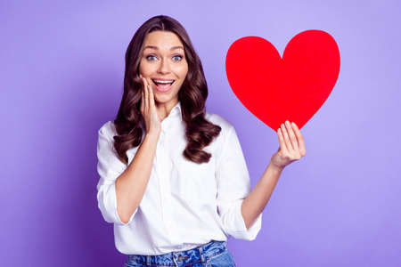 Photo of adorable lady hold heart shape card palm cheek open mouth wear white shirt isolated purple color background