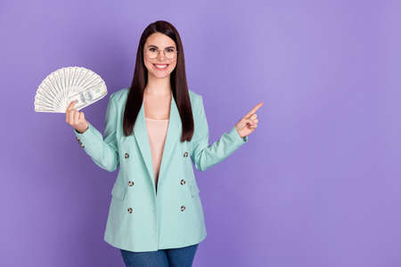 Photo of young happy smiling girl in glasses point finger copyspace hold fan of money isolated on purple color background