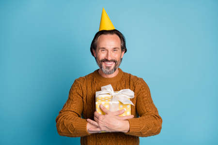 Photo portrait of cheerful smiling man wearing birthday yellow headwear embracing gift isolated on bright blue color background 版權商用圖片