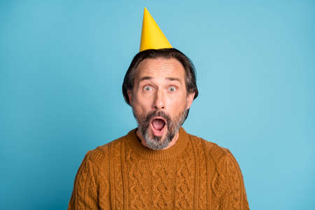 Portrait of mature shocked amazed surprised man with cone on head hear unbelievable news isolated on blue color background 版權商用圖片