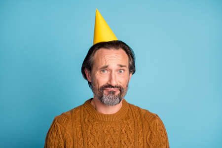 Portrait of unsatisfied person wear birthday cap look camera sullen face isolated on blue color background