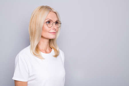 Photo portrait of old lady looking at blank space wearing glasses isolated on grey colored background
