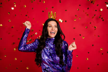 Photo of happy stunning brown haired woman raise fists wear crown look empty space isolated on red color background