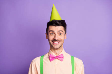 Photo of charming pretty young man dressed yellow shirt birthday headwear smiling isolated purple color background