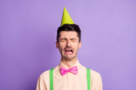 Photo of upset offended young guy wear yellow shirt birthday cap crying nobody came isolated violet color background