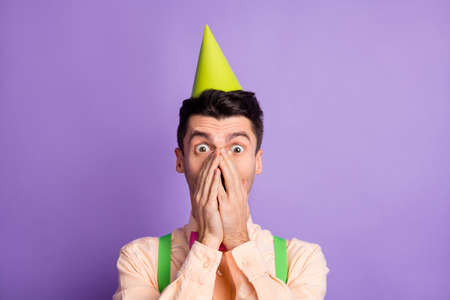 Photo of pretty shocked young man dressed yellow shirt birthday headwear arms cover mouth lips isolated purple color background