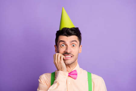 Photo of scared nervous young guy wear yellow shirt birthday cap biting fingers isolated violet color background