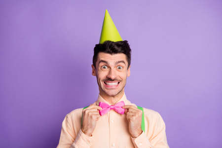 Photo of excited funny young guy wear yellow shirt birthday cap correcting bow tie ready for party isolated violet color background 版權商用圖片