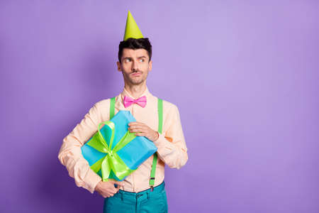 Photo of unsure man dressed yellow shirt birthday headwear holding present looking empty space isolated purple color background