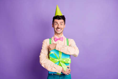 Photo of charming funny man dressed yellow shirt birthday headwear hugging present smiling isolated purple color background