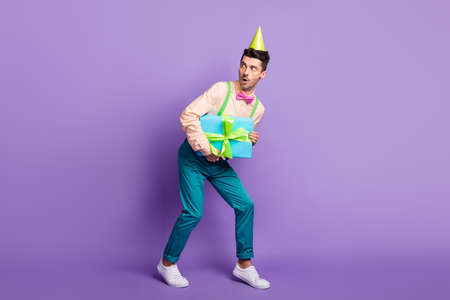 Photo of scared nervous young guy wear yellow shirt birthday cap stealing gift looking empty space isolated violet color background 版權商用圖片