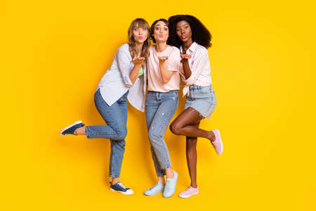 Full size portrait of three adorable persons arm palm send air kiss camera you isolated on yellow color background