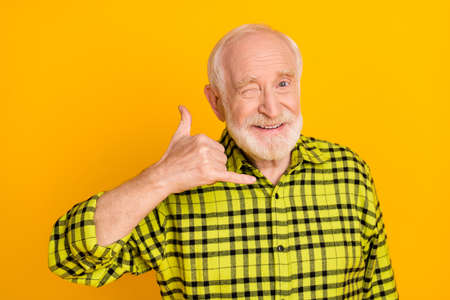 Photo of aged man happy positive smile show finger call phone sign wink eye isolated over yellow color background
