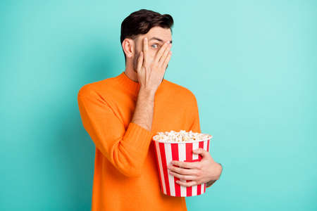 Photo of young guy close cover face hand hold popcorn box watch horror movie scared isolated over teal color background
