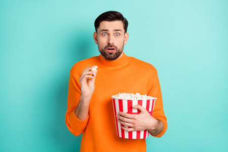 Photo of young guy afraid scared frightened eat popcorn watch horror film isolated over teal color background