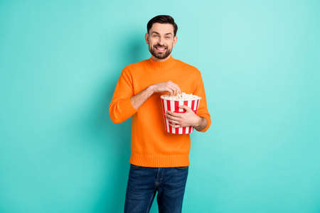 Photo of young man happy positive smile eat popcorn watch movie film isolated over teal color background