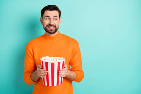 Photo of young handsome man happy positive toothy smile hold popcorn box cinema look empty space isolated over teal color background