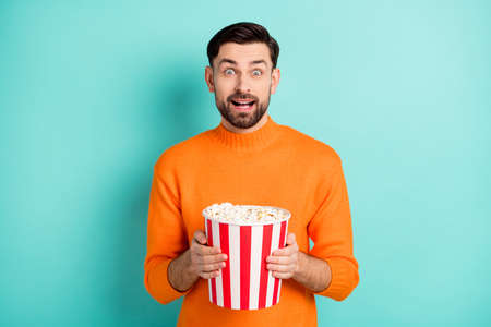 Photo of young excited man amazed shocked surprised hold popcorn box watch movie isolated over turquoise color background