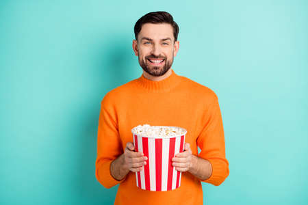 Photo of young cheerful man happy positive smile hold popcorn box watch film isolated over turquoise color background