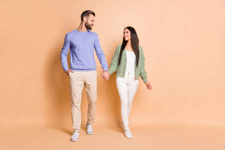 Full length body size view of attractive cheerful couple soulmates strolling holding hands isolated over beige pastel color background