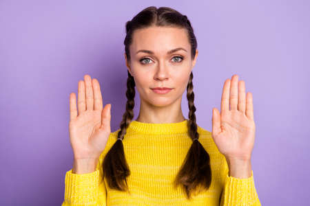 Portrait of strict brunette girl show stop wear yellow sweater isolated on pastel lilac color background