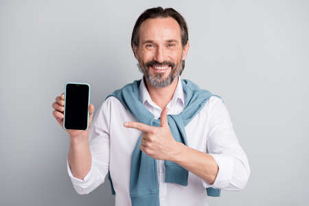 Photo of cheerful mature guy dressed white shirt pullover shoulders pointing finger modern device isolated grey color background