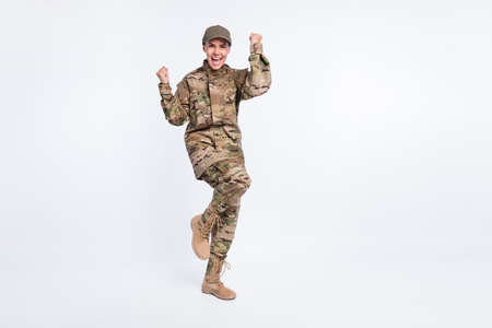 Full size photo of young woman soldier happy positive smile rejoice win victory fists hands isolated over white color background