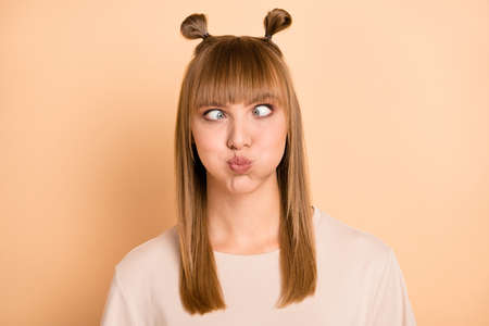 Photo of childish playful stupid girl inflate cheeks squint wear t-shirt isolated beige color background Stock Photo